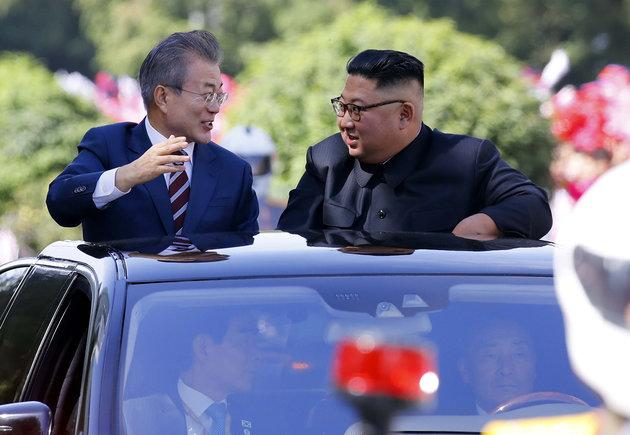 South Korean President Moon Jae-in, left, and North Korean leader Kim Jong-un ride in a car parade in Pyongyang on Tuesday.