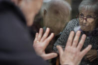 Javier Anto, 90, reacts in front of his wife Carmen Panzano, 92, through the window separating the nursing home from the street in Barcelona, Spain, Wednesday, April 21, 2021. Since the pandemic struck, a glass pane has separated _ and united _ Javier and Carmen for the first prolonged period of their six-decade marriage. Anto has made coming to the street-level window that looks into the nursing home where his wife, since it was closed to visits when COVID-19 struck Spain last spring. (AP Photo/Emilio Morenatti)
