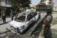 Security personnel inspect a damaged vehicle where rockets were launched in Kabul, Afghanistan, Tuesday, July 20, 2021. At least three rockets hit near the presidential palace on Tuesday shortly before Afghan President Ashraf Ghani was to give an address to mark the Muslim holiday of Eid-al-Adha. (AP Photo/Rahmat Gul)