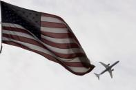 FILE PHOTO: A Delta Airlines flight takes off past a U.S. flag in Boston