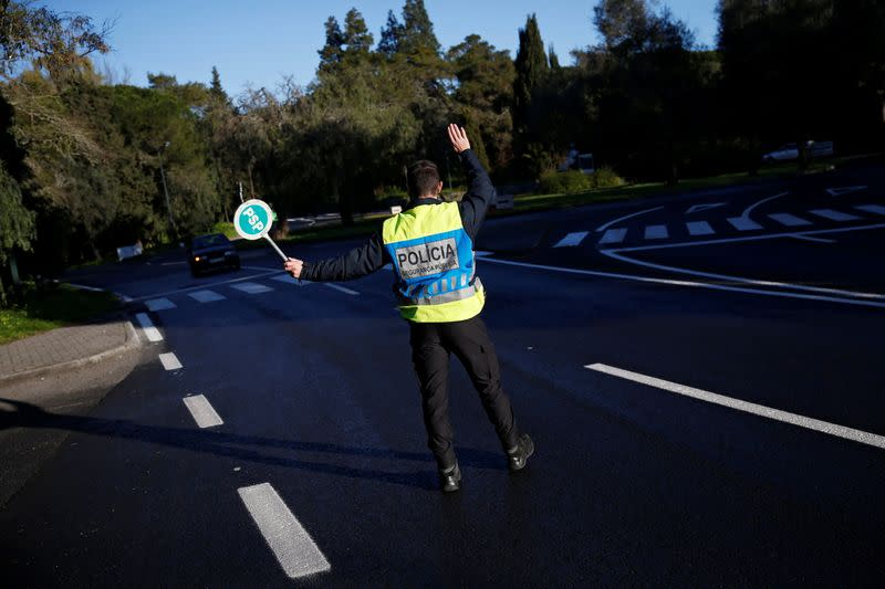 A police officer stops a car at a checkpoint for control on the first day of the second national lockdown due to the coronavirus disease (COVID-19) pandemic in Lisbon
