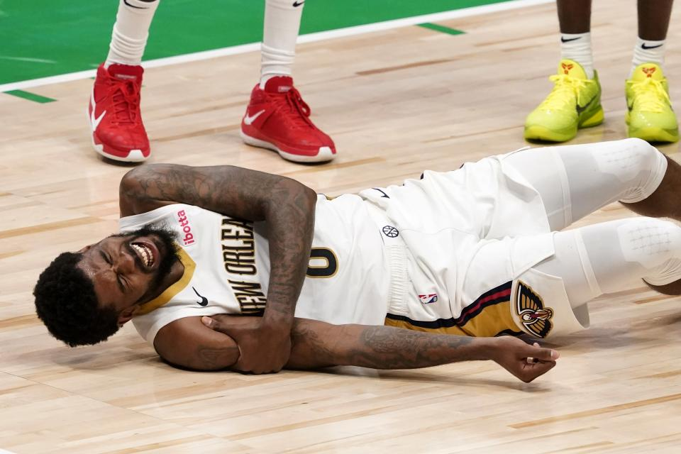 New Orleans Pelicans forward Naji Marshall rolls on the court while holding on to his right arm after colliding with Dallas Mavericks' Dorian Finney-Smith during the second half of an NBA basketball game in Dallas, Wednesday, May 12, 2021. Marshall left the game. (AP Photo/Tony Gutierrez)