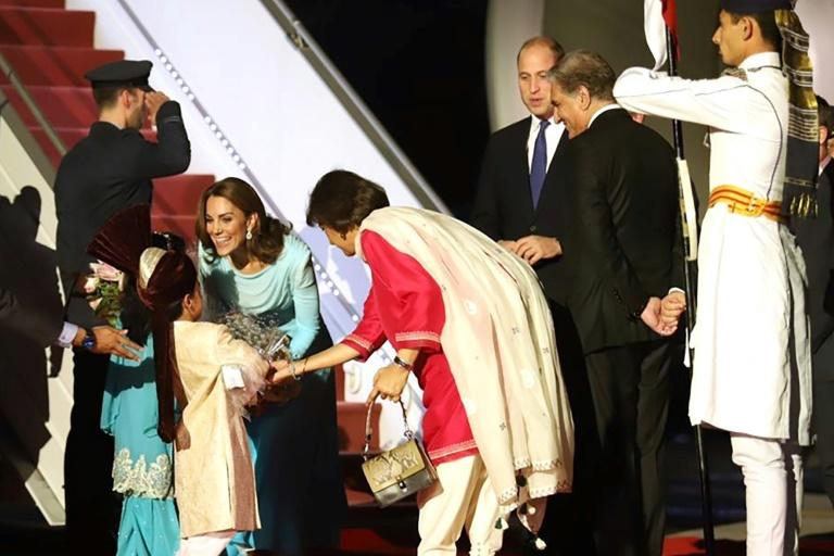 Britain's Prince William, Duke of Cambridge (3R), and his wife Kate (2L) receive flowers from Pakistani children after arriving at a military airbase in Rawalpindi for the first visit by British royals since 2006