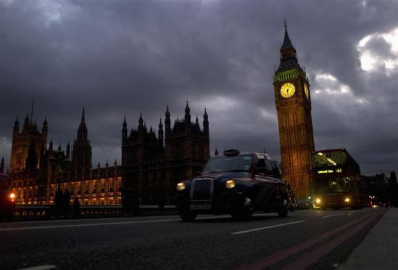 A bus and taxi pass Big Ben on Westminster Bridge in London March 10, 2012.