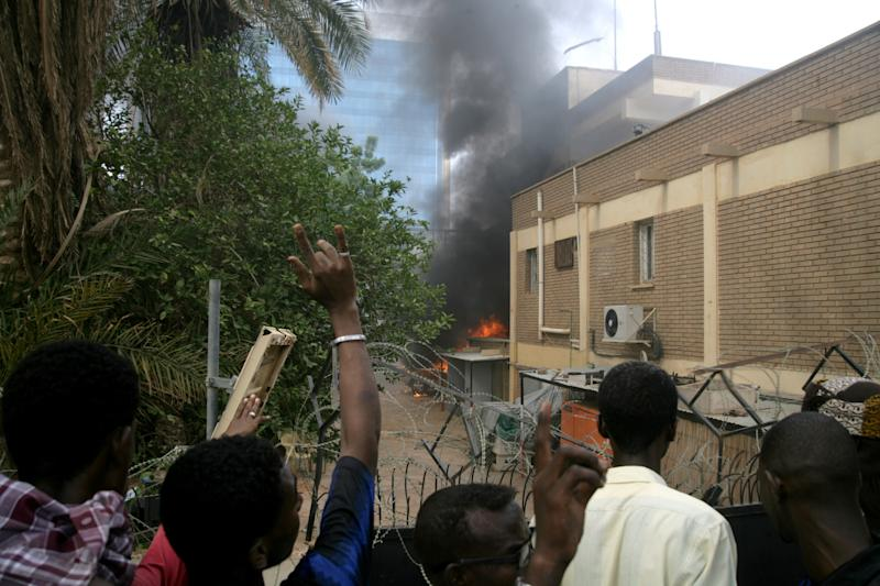 Sudanese protesters react as a fire rages during a protest outside the German embassy in Khartoum, Sudan, Friday, Sept. 14, 2012, as part of widespread anger across the Muslim world about a film ridiculing Islam's Prophet Muhammad. Germany's Foreign Minister says the country's embassy in the Sudanese capital of Khartoum has been stormed by protesters and set partially on fire. Minister Guido Westerwelle told reporters that the demonstrators are apparently protesting against an anti-Islam film produced in the United States that denigrates the Prophet Muhammad.(AP Photo/Abd Raouf)