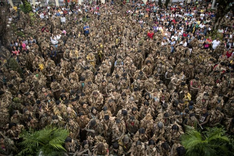 Hundreds of Filipino Catholic devotees covered themselves in mud and banana leaves