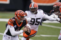 Cincinnati Bengals quarterback Joe Burrow (9) is chased by Cleveland Browns defensive end Myles Garrett (95) during the first half of an NFL football game, Sunday, Oct. 25, 2020, in Cincinnati. (AP Photo/Michael Conroy)