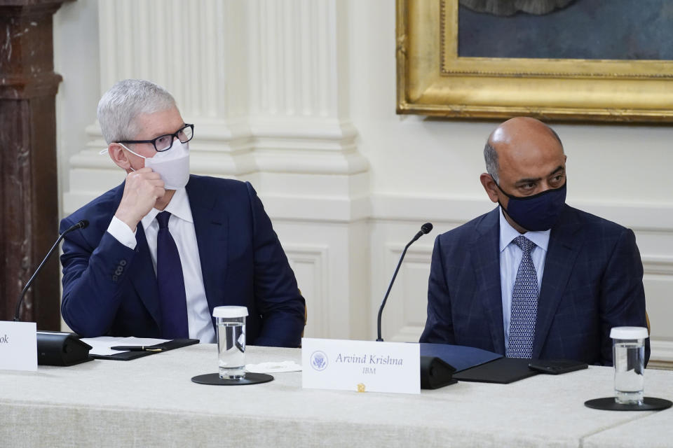 Apple CEO Tim Cook, left, and IBM CEO Arvind Krishna listen as President Joe Biden speaks during a meeting about cybersecurity in the East Room of the White House, Wednesday, Aug. 25, 2021, in Washington. (AP Photo/Evan Vucci)