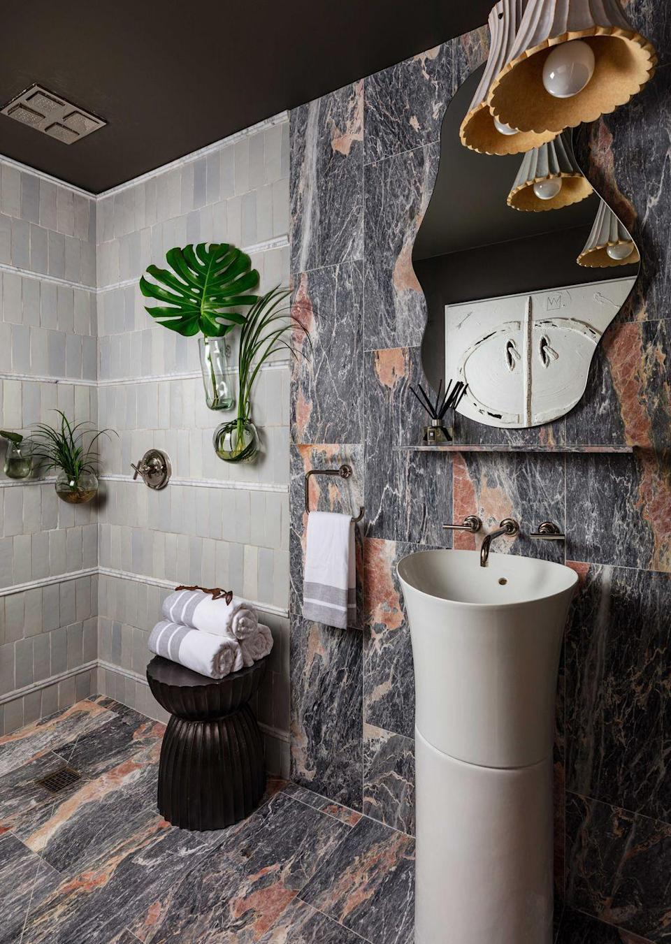 <p>This bathroom by Tavia Forbes and Monet Masters of Atlanta-based Forbes+Masters is the ultimate exercise in thinking outside the lines. Instead of confining materials to certain zones, they pushed the envelope, spreading a dramatic marble from the floor up to the wall in one half of the space and a soft, sage terra cotta on the other. Polished nickel Kohler fixtures add shine, while <strong>wall-hung vases holding tropical greenery give a spa-like feel. </strong></p>