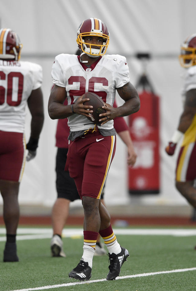 Washington Redskins running back Adrian Peterson carries the ball during an NFL football team practice, Tuesday, Aug. 21, 2018, in Ashburn, Va. (AP Photo/Nick Wass)