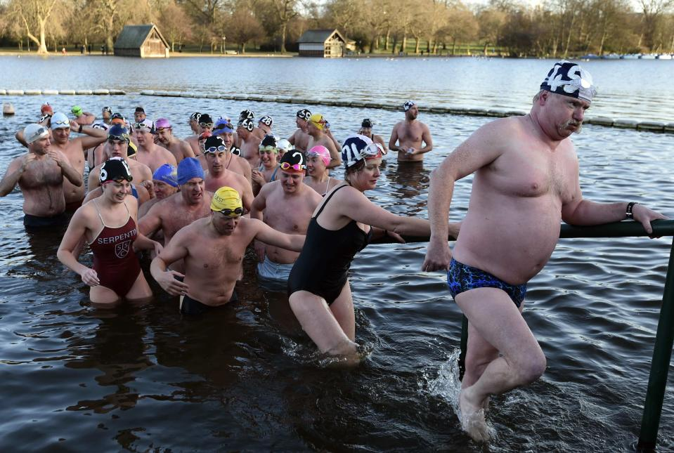 Competitors climb out of the water after taking part in the Peter Pan Cup open water swim in the Serpentine Lake at Hyde Park in London, December 25, 2014. Over one hundred swimmers took part in the annual Christmas Day event, swimming in water temperatures of 3-5 degrees celsius. REUTERS/Toby Melville (BRITAIN - Tags: SOCIETY ENVIRONMENT SPORT SWIMMING)