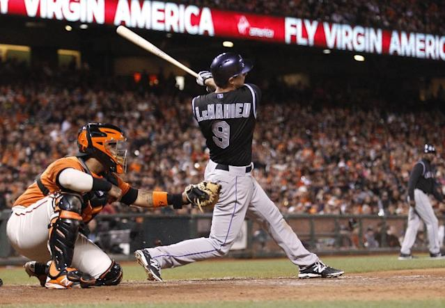 Colorado Rockies' DJ LeMahieu hits an RBI single in the ninth inning during a baseball game against the San Francisco Giants in San Francisco, Friday, June 13, 2014. (AP Photo/Beck Diefenbach)