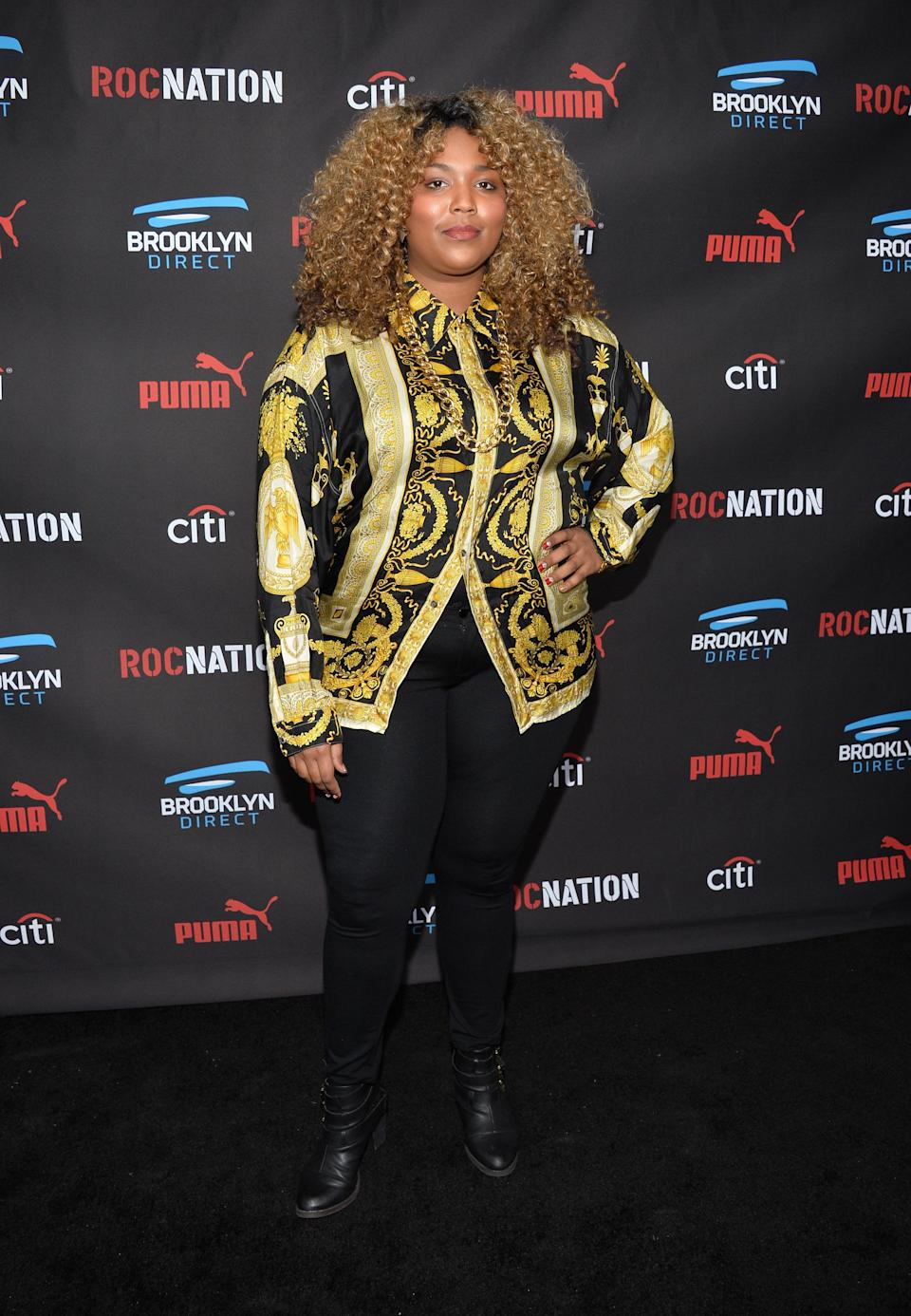 Lizzo was spotted wearing a black and gold Versace top with black pants to the 2015 Roc Nation Brunch. She's definitely come a long way since then!