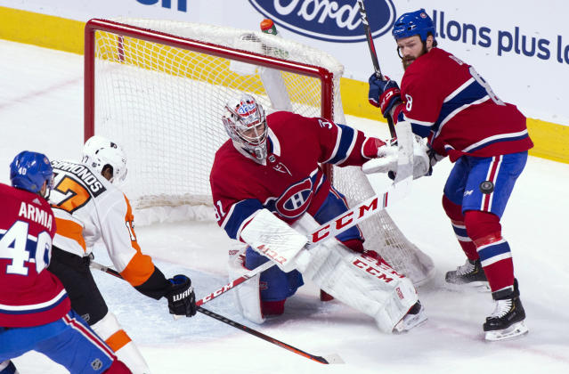 Montreal Canadiens goaltender Carey Price watches a shot deflected off Philadelphia Flyers' Wayne Simmonds as Canadiens' Jordie Benn (8) looks for the puck during the first period of an NHL hockey game Thursday, Feb. 21, 2019, in Montreal. (Paul Chiasson/The Canadian Press via AP)