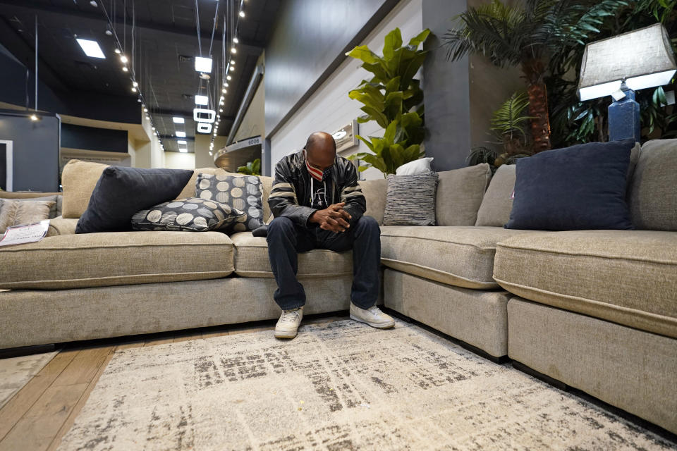 Charvis Johnson sits on a couch inside a Gallery Furniture store which opened as a shelter Wednesday, Feb. 17, 2021, in Houston. Millions in Texas still had no power after a historic snowfall and single-digit temperatures created a surge of demand for electricity to warm up homes unaccustomed to such extreme lows, buckling the state's power grid and causing widespread blackouts. (AP Photo/David J. Phillip)