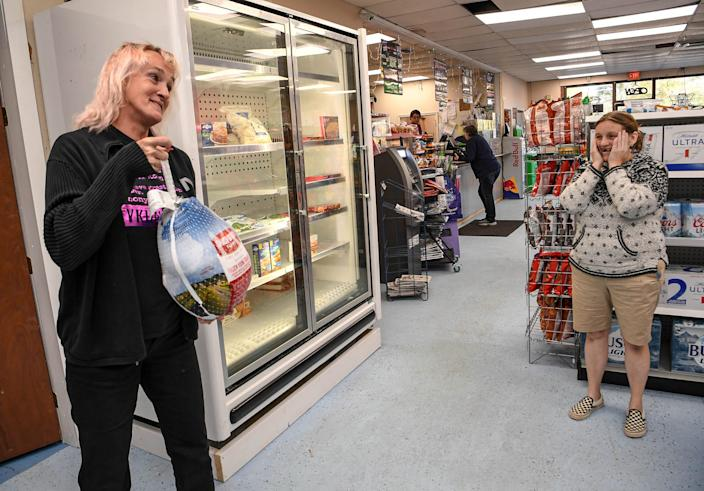 Aggi Tarnowski, left, store manager at the KP Food Mart in Anderson, South Carolina, shows Melissa Grimmette one of the donated frozen turkeys the store will help prepare for Thanksgiving. A $350,000 winning lottery scratch-off ticket was sold at the store, which also meant the store got $3,500. Tarnowski said the store would put the money back into having Thanksgiving meals to go for the community. Locals also donated food for the Thanksgiving meals, which the store owners say they will match.