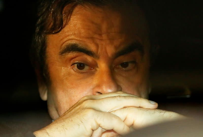 FILE PHOTO: Former Nissan Motor Chairman Carlos Ghosn sits inside a car as he leaves his lawyer's office after being released on bail from Tokyo Detention House, in Tokyo