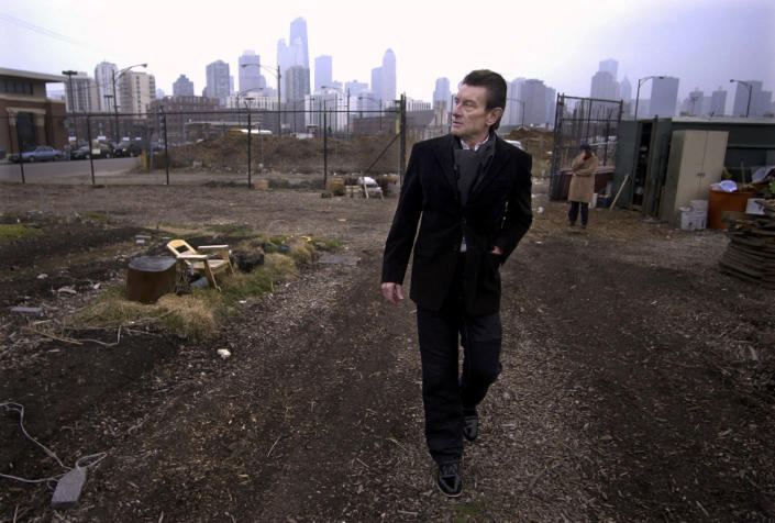 FILE - In this March 4, 2004 file photo, architect Helmut Jahn walks through a vacant lot on Chicago's near north side. Jahn, a prominent German architect who designed an Illinois state government building and worked on the design of the FBI headquarters in Washington, was killed when two vehicles struck the bicycle he was riding outside Chicago. Jahn, 81, was struck Saturday, May 8, 2021, afternoon while riding north on a village street in Campton Hills, about 55 miles (90 kilometers) west of Chicago. (AP Photo/M. Spencer Green File)