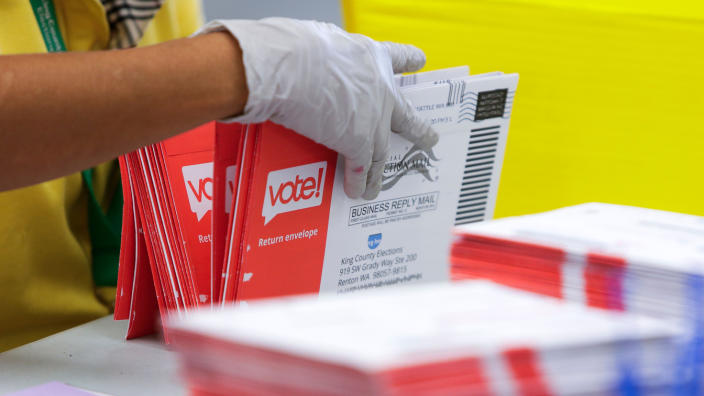 An election worker opens envelopes containing vote-by-mail ballots