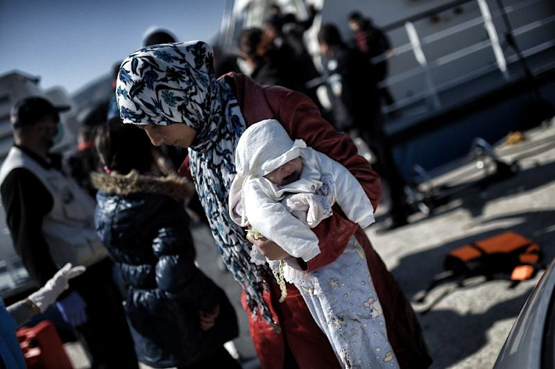 A woman carries her baby as migrants and refugees disembark from a Frontex ship at the port of the northern island of Lesbos after crossing the Aegean sea from Turkey (AFP Photo/Aris Messinis)