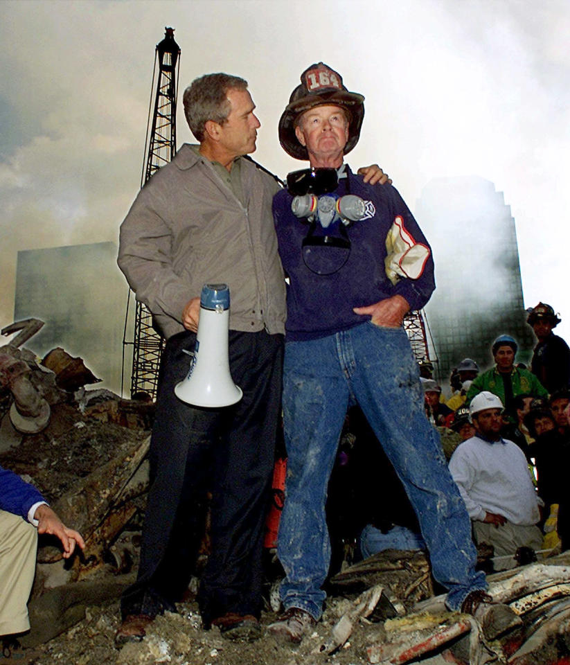 FILE - In this Sept. 14, 2001 file photo, President George W. Bush puts his arms around firefighter Bob Beckwith while standing in front of the World Trade Center in New York during a tour of the devastation. George W. Bush knows that history will shape his legacy more than anything he can say. But that's not gonna stop a guy from trying. After two years of near silence, Bush is back. With his new memoir and a promotion tour, the president who in cockier times could not think of a single mistake he had made, lists many.