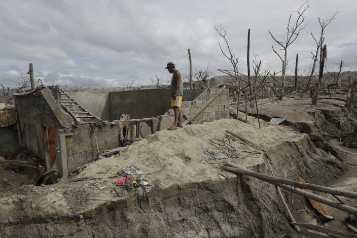 Fisherman Rogelito Cacao looks at the remains of his house at the Taal volcano almost a year after it erupted on Sunday, Jan. 10, 2021 in Batangas province, Philippines. Cacao regularly visits the area after feeding fish at the pens on the Taal lake. A popular tourist destination just south of Manila because of its picturesque setting in the middle of a lake, Taal erupted on Jan. 12, 2020. The eruption displaced thousands of villagers living near the area and delivered an early crisis this year for one of the world's most disaster-prone nations a couple of months before the COVID-19 pandemic broke in the country. (AP Photo/Aaron Favila)