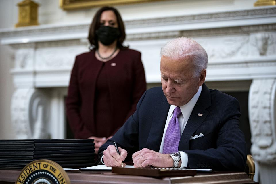 President Joe Biden signs an executive order with U.S. Vice President Kamala Harris (Al Drago/Bloomberg via Getty Images)