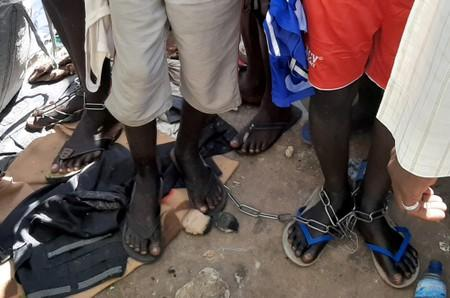 People with chained legs are pictured after being rescued by police in Sabon Garin