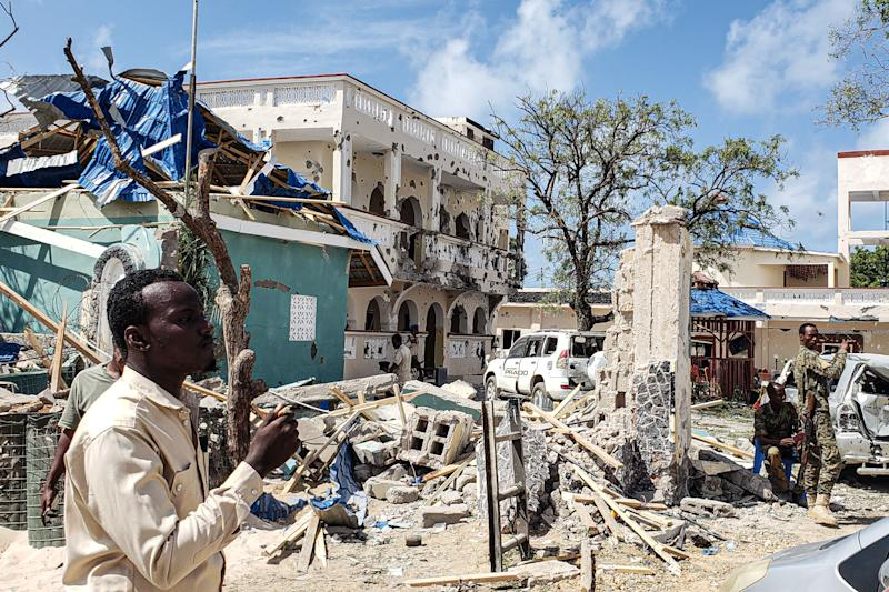 A man passes in front of the rubbles of the popular Medina hotel of Kismayo on July 13, 2019, a day after dozens were killed and over 50 people injured in a suicide bomb and gun attack claimed by Al-Shabaab militants. (Photo: Stringer/AFP/Getty Images)