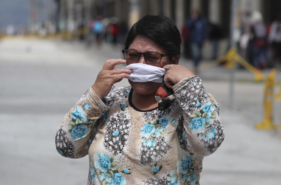 A woman hurriedly places a protective face mask over her mouth and nose to avoid a $100.00 US dollar fine, as wearing a face mask in public is mandatory, in Quito, Ecuador, Wednesday, June 10, 2020. The city is returning to a new normality after relaxing a rigorous quarantine but amid a certain fear that new coronavirus infections may rise. (AP Photo/Dolores Ochoa)