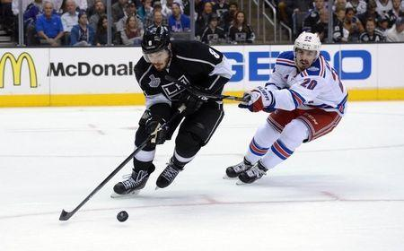 Jun 4, 2014; Los Angeles, CA, USA; Los Angeles Kings defenseman Drew Doughty (8) reaches for the puck against New York Rangers left wing Chris Kreider (20) in the second period during game one of the 2014 Stanley Cup Final at Staples Center. Mandatory Credit: Kirby Lee-USA TODAY Sports