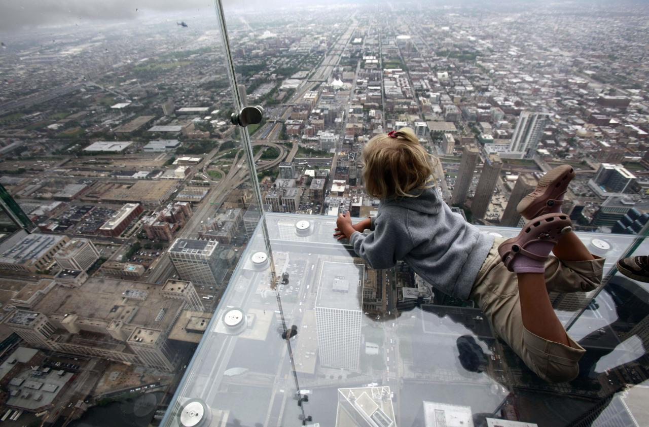 "FILE - In this June 24, 2009, file photo Anna Kane, 5, looks down from ""The Ledge,"" at Chicago's 110 story, 1,450 foot Willis Tower. The glass balcony is suspended 1,353 feet in the air and juts out 4 feet from the Sears Tower's 103rd floor Skydeck. The Tower is in contention with the 104-story, 1,776 foot One World Trade Center, a skyscraper built at the site of the 9/11 attacks on the World Trade Center in New York as the tallest building in America. A committee of architects recognized as the arbiters on world building heights is meeting Friday Nov. 8, 2013 in Chicago to decide whether a design change affecting One World Trade Center's needle disqualifies its hundreds of feet from being counted, which would deny the building the title of nation's tallest giving the title to Willis Tower. (AP Photo/Kiichiro Sato, File)"