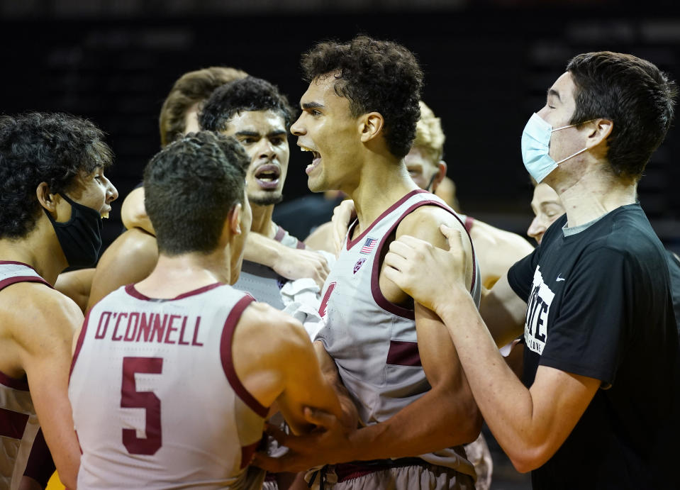Stanford forward Oscar da Silva, center, celebrates with teammates after scoring in overtime for a victory in an NCAA college basketball game against UCLA in Santa Cruz, Calif., Saturday, Jan. 23, 2021. (AP Photo/Tony Avelar)