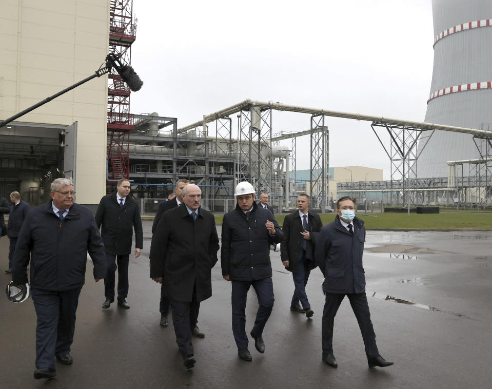 """Belarusian President Alexander Lukashenko, centre, attends the first Belarusian Nuclear Power Plant during the plant's power launch event outside the city of Astravets, Belarus, Saturday, Nov. 7, 2020. Alexander Lukashenko on Saturday formally opened the country's first nuclear power plant, a project sharply criticized by neighboring Lithuania. Lukashenko said the launch of the Russian-built and -financed Astravyets plant """"will serve as an impetus for attracting the most advanced technologies to the country. and innovative directions in science and education."""" (Maxim Guchek/BelTA Pool Photo via AP)"""