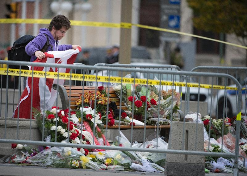 People pay their respects at National War Memorial on October 23, 2014, in Ottawa, the day after multiple shootings in the capital city and Parliament buildings left a soldier dead and others wounded (AFP Photo/Peter McCabe)
