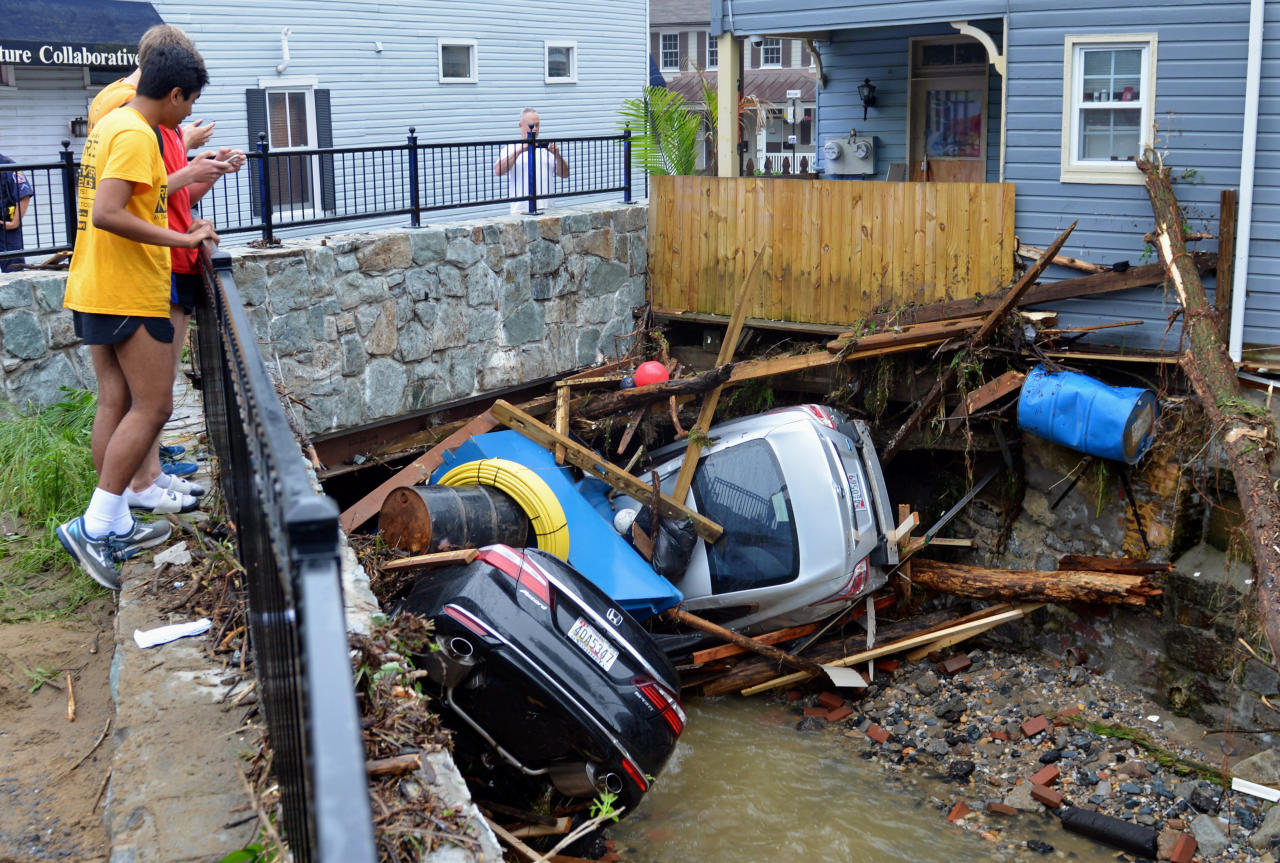 <p>Residents gather by a bridge to look at cars left crumpled in one of the tributaries of the Patapsco River that burst its banks as it channeled through historic Main Street in Ellicott City, Md., Monday, May 28, 2018. (Photo: David McFadden/AP) </p>