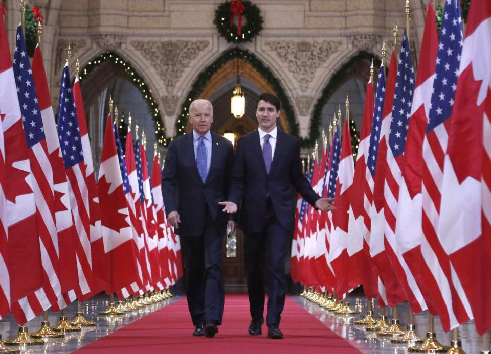 Joe Biden and Justin Trudeau walk down the Hall of Honour on Parliament Hill in Ottawa, flanked by Canadian and American flags.