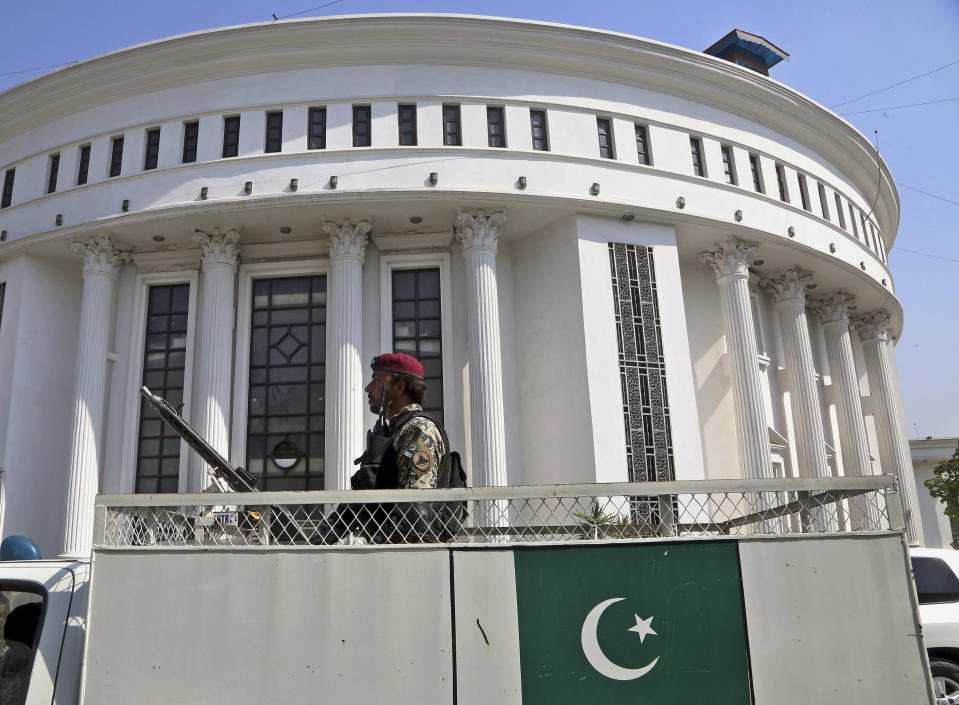 A paramilitary soldier guards outside the provincial assembly building as lawmakers arrive to cast their vote in senate elections, at the provincial assembly, in Peshawar, Pakistan, Wednesday, March 3, 2021. Pakistani lawmakers are choosing new members of the country's Senate, or upper house of parliament — a vote that is seen as a test for Prime Minister Imran Khan's government. Khan's ruling Pakistan Tehreek-e-Insaf party is seeking to improve its standing in the 104-member Senate, where it lacks a majority. (AP Photo/Muhammad Sajjad)