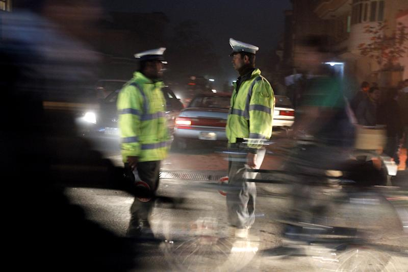 Afghan traffic policemen stand near the scene where Afghanistan's Intelligence Chief Asadullah Khalid was wounded in an assassination attempt on him in Kabul, Afghanistan, Thursday, Dec. 6, 2012. Afghanistan's intelligence chief was wounded Thursday in an assassination attempt in the capital, Kabul, Afghan officials said. (AP Photo/Ahmad Jamshid)