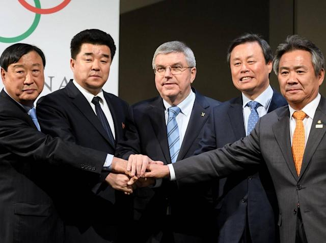 Delegates from both countries join hands with the IOC president Thomas Bach (Getty)