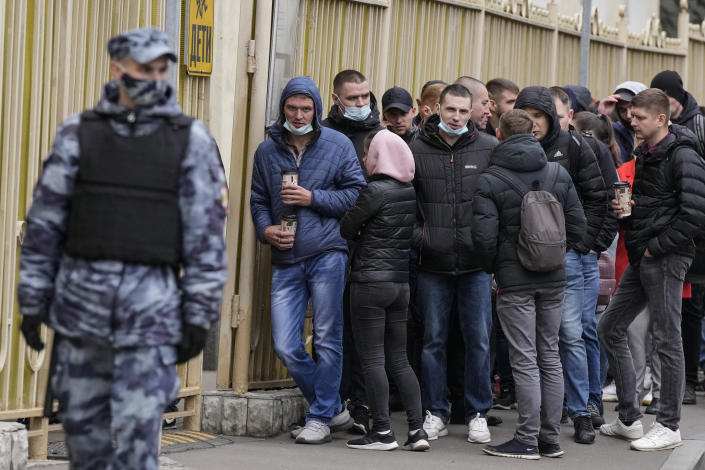 A Russian Rosguardia (National Guard) soldier guards as people queue to cast their votes at the entrance of a polling station during parliamentary elections in Moscow, Russia, Friday, Sept. 17, 2021. Russia has begun three days of voting for a new parliament that is unlikely to change the country's political complexion. There's no expectation that United Russia, the party devoted to President Vladimir Putin, will lose its dominance in the State Duma. (AP Photo/Pavel Golovkin)