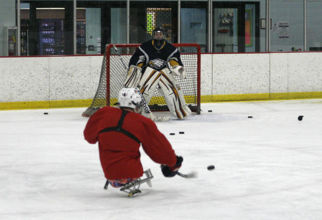 Brody Roybal, 15, shoots a goal during a practice with his high school hockey team in Franklin Park, Ill., on Tuesday, Feb. 11, 2014. He's been playing sled hockey since he was 7. (AP Photo/Martha Irvine)