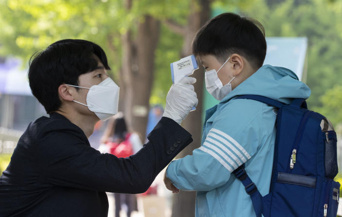 Image: A student gets body temperature measured when returning for classes at Seryun Elementary School in Seoul, South Korea (Lee Sang-ho/Xinhua / Getty Images file)