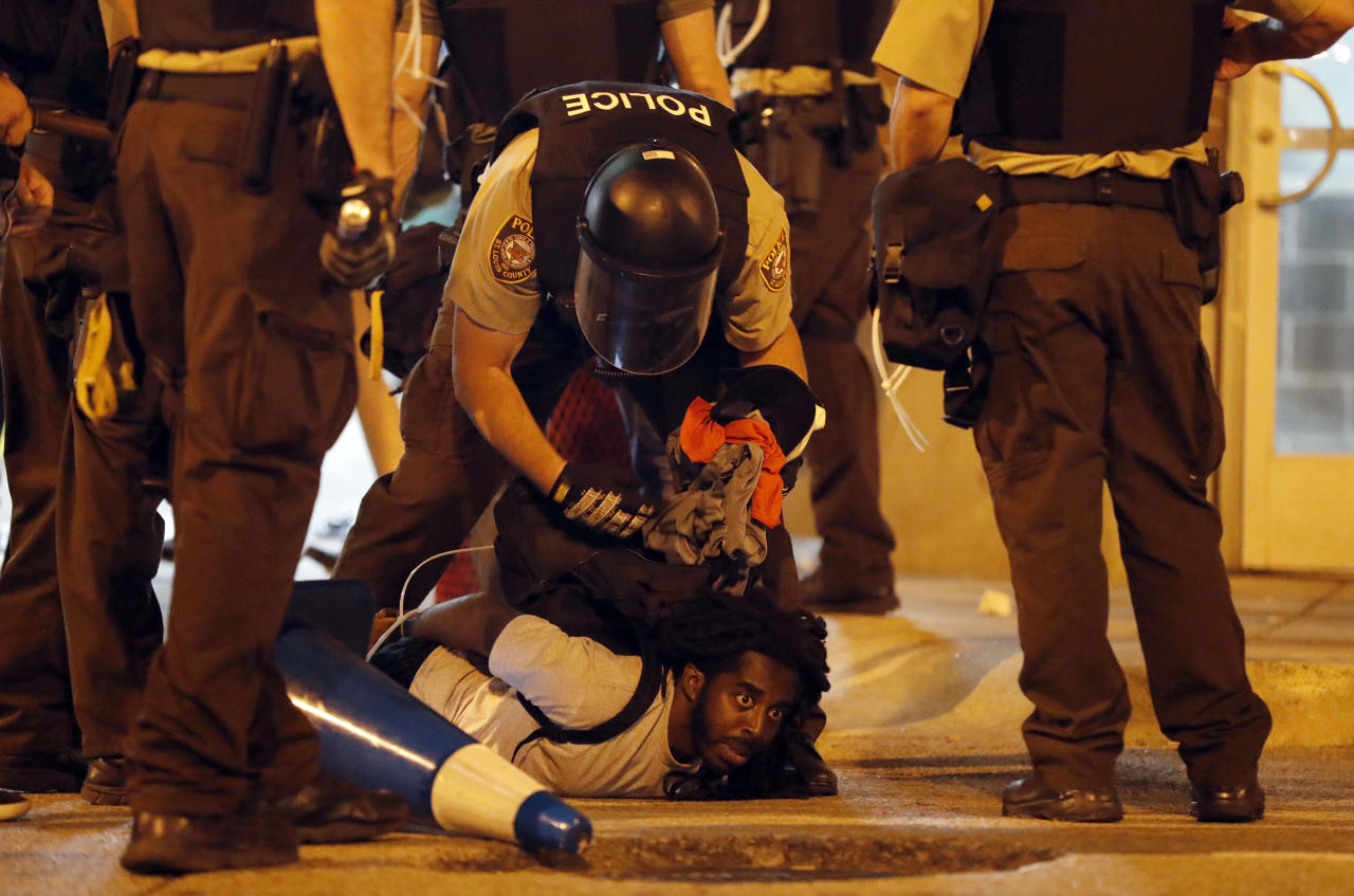<p>Police arrest a man as demonstrators march in response to a not guilty verdict in the trial of former St. Louis police officer Jason Stockley, Sunday, Sept. 17, 2017, in St. Louis. Stockley was acquitted in the 2011 killing of a black man following a high-speed chase. (Photo: Jeff Roberson/AP) </p>