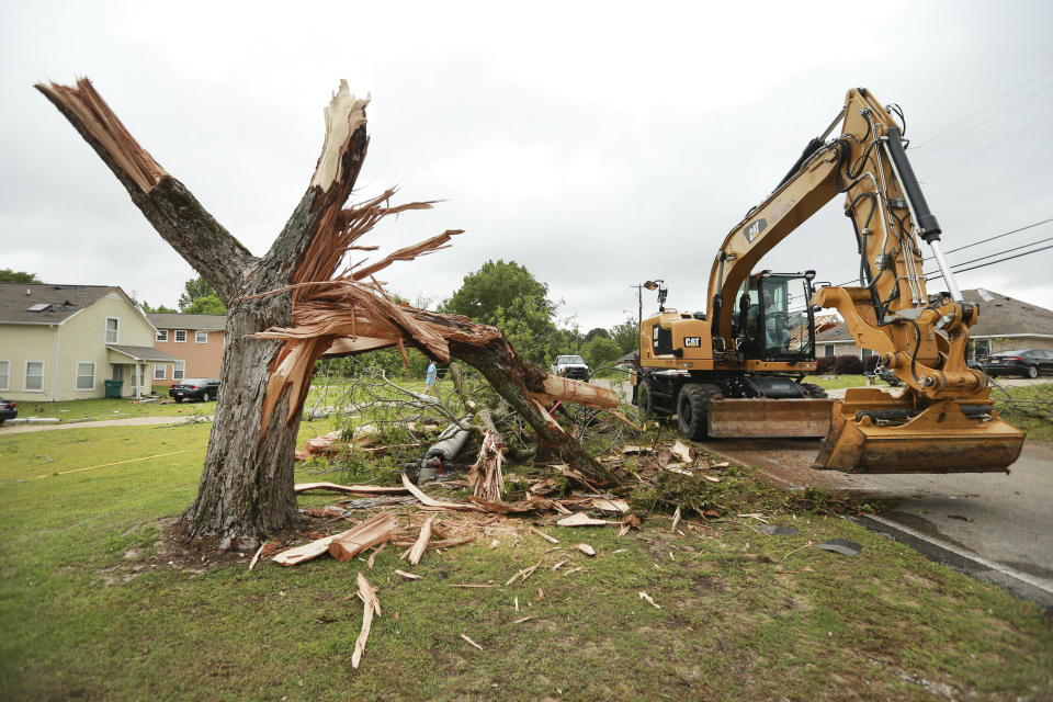 A Tupelo Public Works employee works to clear out more debris and tree limbs on Monday, May 3, 2021 after a tornado hit the area late Sunday night in Tupelo, Miss. (Adam Robison/The Northeast Mississippi Daily Journal via AP)