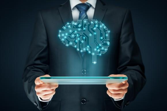 Man holding a tablet that's projecting a brain representing AI.