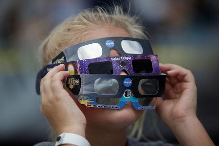 Ariana Mareyev, 10, of Charleston wears several pairs of solar glasses on the flight deck of the Naval museum ship U.S.S. Yorktown in Mount Pleasant, South Carolina. REUTERS/Randall Hill