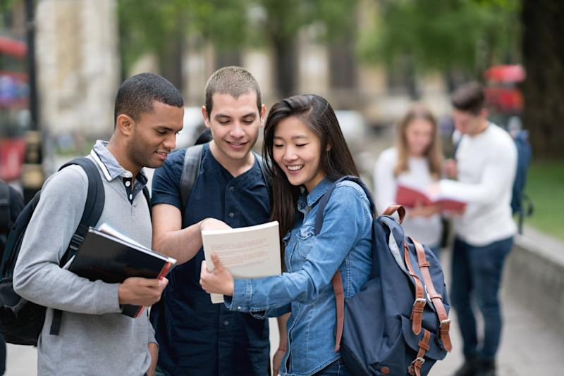 Portrait of a happy multi-ethnic group of students studying outdoors and smiling - education concepts