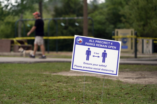 A sign is posted in a park reminding people to practice social distancing Wednesday, March 25, 2020, in Houston, Texas. (AP Photo/David J. Phillip)