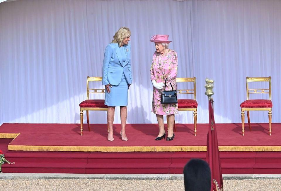 <p>For the occasion, Dr. Jill Bidn wore a powder blue suit and nude heels while the Queen wore a pink floral dress and a matching hat. </p>
